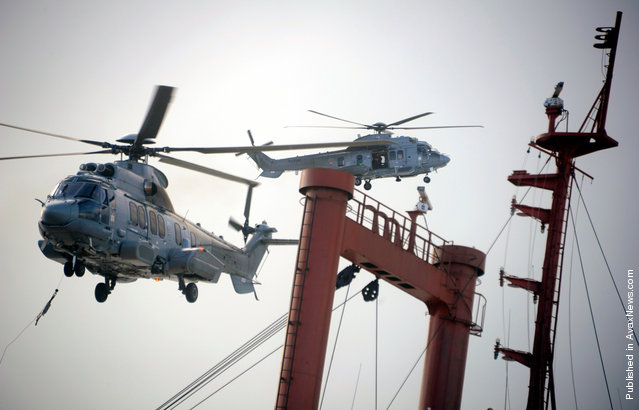 """AS332 """"Super Puma"""" helicopters fly over the TK Bremen cargo ship on Kerminihy beach in Erdeven, on December 16, 2011"""