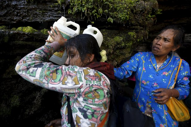 Hindu villagers collect holy water from a stream for prayers ahead of the annual Kasada festival at Mount Bromo in Indonesia's East Java province, July 31, 2015. (Photo by Reuters/Beawiharta)