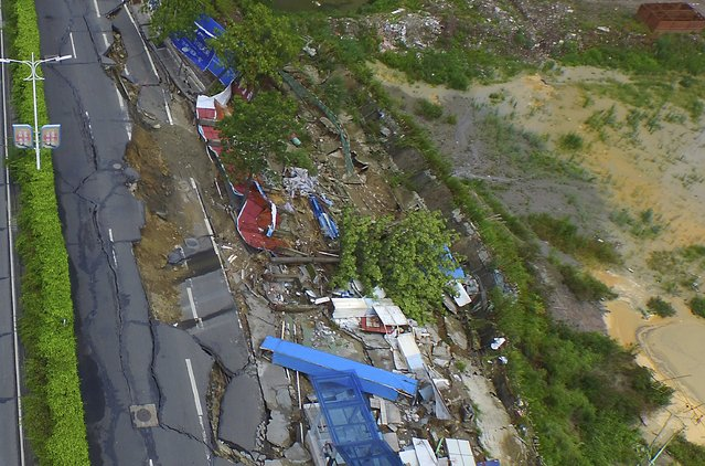 An aerial view shows parts of a street next to a construction site collapse, in Foshan, Guangdong province, China, July 26, 2015. The approximately 60-metre-long, 15-metre-wide cave-in occurred on Sunday morning, blocking part of the street. No one was injured during the incident, local media reported. (Photo by Guo Jijiang/Reuters/Southern Metropolis Daily)
