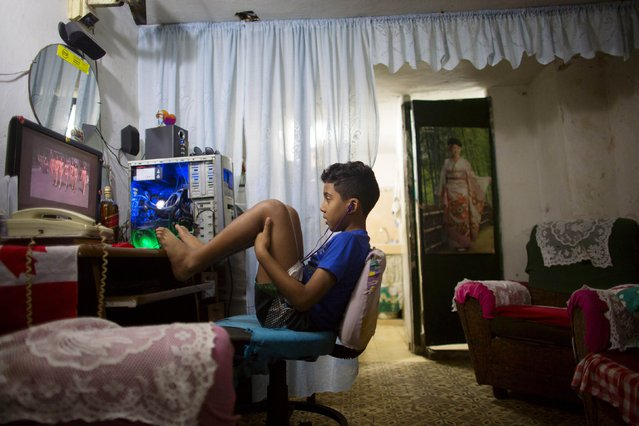 Kevin Lachaise, 8, watches a recorded TV show through the screen of a computer at the living room of his home in downtown Havana February 10, 2015. Netflix Inc launched its movie and TV streaming service in Cuba on Monday, joining the list of U.S. companies looking to take advantage of thawing diplomatic relations between the United States and the communist-ruled island country. (Photo by Alexandre Meneghini/Reuters)
