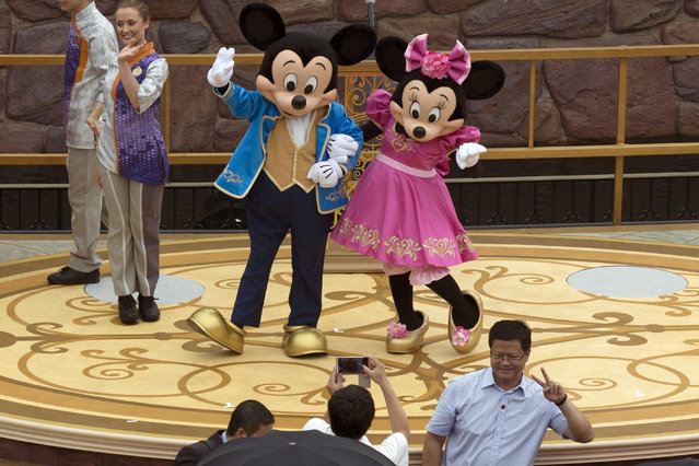 Mickey and Minnie Mouse pose for a photograph at the opening ceremony for the Disney Resort in Shanghai, China, Thursday, June 16, 2016. Walt Disney Co. opened its first theme park in mainland China on Thursday at a ceremony that mixed speeches by Communist Party officials, a Chinese children's choir and actors dressed as Sleeping Beauty and other Disney characters. (Photo by Ng Han Guan/AP Photo)