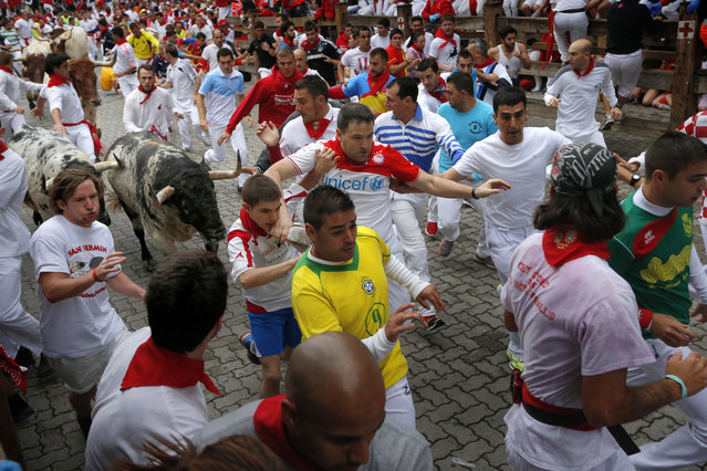 """Revelers are chased by fighting bulls during the running of the bulls of the San Fermin festival, in Pamplona, Spain, Monday, July 7, 2014. Revelers from around the world arrive here to take part in the eight-day event glorified by Ernest Hemingway's 1926 novel """"The Sun Also Rises"""". (Photo by Daniel Ochoa de Olza/AP Photo)"""