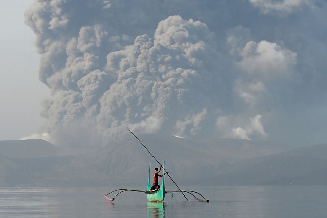 "A youth living at the foot of Taal volcano rides an outrigger canoe while the volcano spews ash as seen from Tanauan town in Batangas province, south of Manila, on January 13, 2020. The Philippines was on alert January 13 for the ""explosive eruption"" of a volcano south of Manila, which officials said could be imminent after a massive column of ash forced a halt to flights at the capital's main airport. (Photo by Ted Aljibe/AFP Photo)"