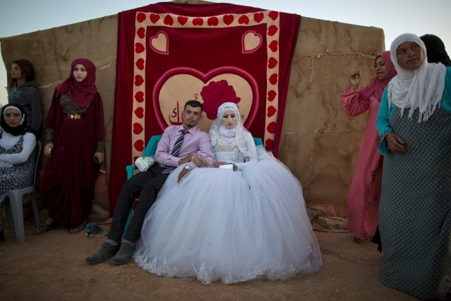 Syrian refugee groom Ahmad Khalid, 21, and his bride Fatheya Mohammed, 21, sit in front of his family's tent during their wedding ceremony at an informal tented settlement near the Syrian border on the outskirts of Mafraq, Jordan, Friday, August 7, 2015. (Photo by Muhammed Muheisen/AP Photo)