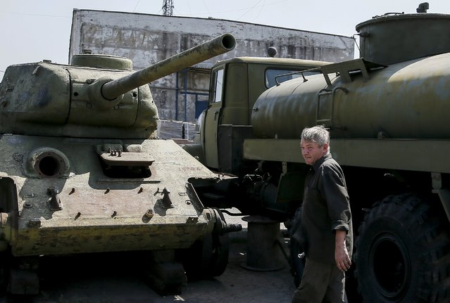 A worker looks at an old soviet tank T-34 (L) as he fixes military vehicle (R) at a Phaeton museum in Zaporizhia, Ukraine, August 11, 2015. (Photo by Gleb Garanich/Reuters)