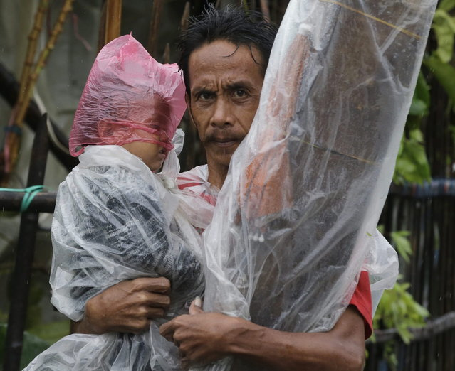 A father and his son evacuate to safer grounds as Typhoon Rammasun battered Manila, Philippines, Wednesday, July 16, 2014. Rammasun left at least seven people dead and knocked out power in many areas but it spared the Philippine capital and densely populated northern provinces from being directly battered Wednesday when its fierce wind shifted slightly away, officials said. (Photo by Bullit Marquez/AP Photo)