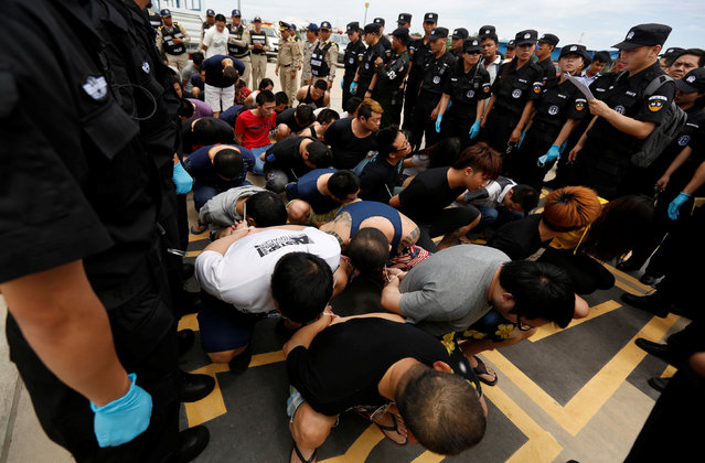 Taiwan's and China's suspects are surrounded by China police SWAT team and Cambodia police before being deported at the International Airport of Phnom Penh, June 24, 2016. Scores of Chinese police officers swarmed the tarmac at Phnom Penh International Airport on Friday as 39 suspects arrested for their involvement in an alleged telecom scam were herded onto a chartered plane bound for China – including 25 Taiwanese nationals, whose government unsuccessfully attempted to have them repatriated. (Photo by Samrang Pring/Reuters)
