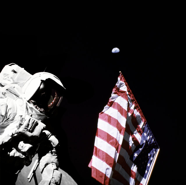 Geologist-Astronaut Harrison Schmitt, Apollo 17 Lunar Module pilot, is photographed next to the American Flag during extravehicular activity (EVA) of NASA's final lunar landing mission in the Apollo series. The photo was taken at the Taurus-Littrow landing site. The highest part of the flag appears to point toward our planet earth in the distant background. (Photo by NASA)