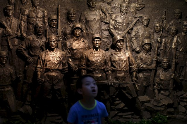 A boy stands in front of a sculpture during a media trip at the Shanghai Songhu Campaign Memorial Hall in Shanghai, August 13, 2015. (Photo by Aly Song/Reuters)