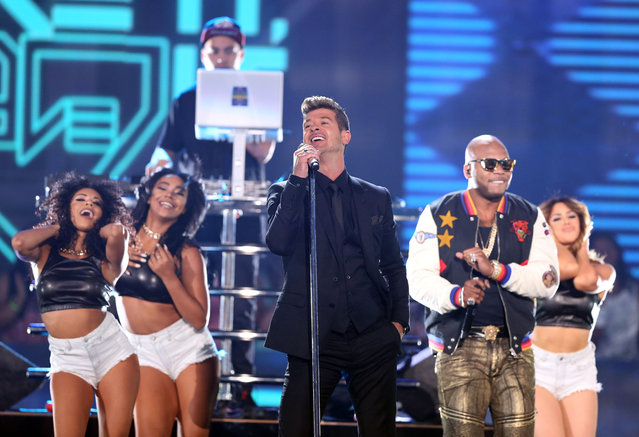 "Robin Thicke, center, and Flo Rida perform ""I Don't Like It, I Love It"" at the Teen Choice Awards at the Galen Center on Sunday, August 16, 2015, in Los Angeles. (Photo by Matt Sayles/Invision/AP Photo)"