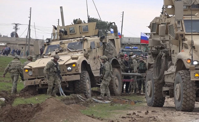 In this frame grab from video, Russian, Syrian and others gather next to an American military convoy stuck in the village of Khirbet Ammu, east of Qamishli city, Syria, Wednesday, February 12, 2020. Syrian media and activists say a Syrian was killed and another wounded in a rare clash between American troops and a group of government supporters in northeast Syria. (Photo by AP Photo/Stringer)