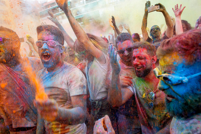 People take part in the fourth edition of the Monsoon Holi Madrid party at the multicultural district of Lavapies, in Madrid, Spain, 05 August 2017. Participants were prayed with thousands of liters of water, tinted with 600 kgs of colored powder. (Photo by EPA/Mariscal)