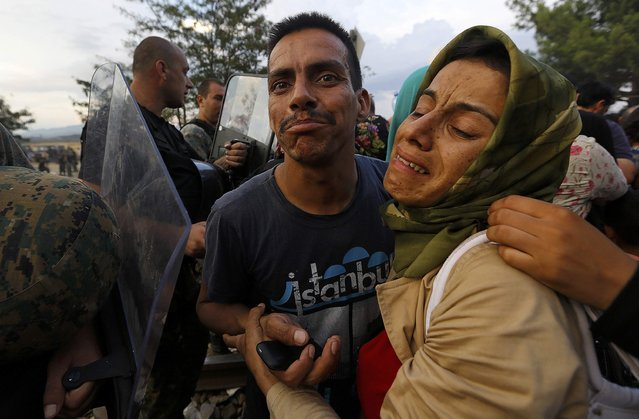 A Syrian refugee woman cries by her husband as she pushed away by Macedonian riot police (L) at the Greek-Macedonian border, near the village of Idomeni, August 21, 2015. (Photo by Yannis Behrakis/Reuters)