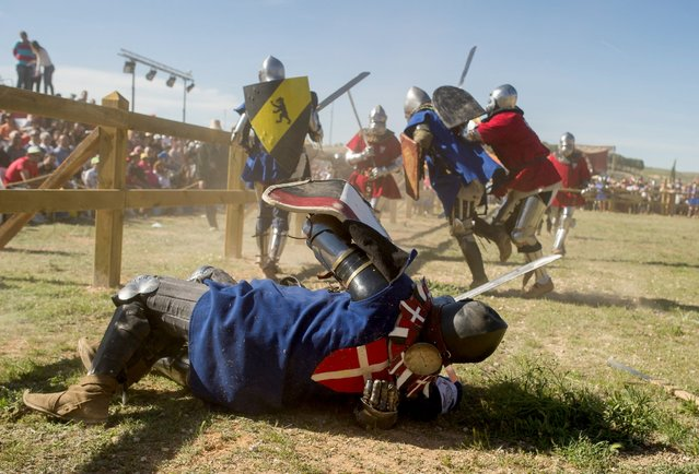A fallen knight of the Danish team look on as his comrades battle with knights of the Polish team during the International Medieval Combat at Belmonte castle, May 1, 2014, in Belmonte, Spain. (Photo by Denis Doyle/Getty Images)