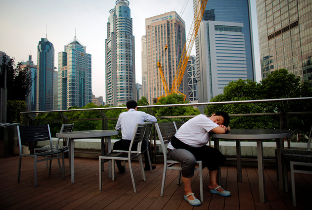 A waitress sleeps as she take a break at a restaurant located in the Pudong financial district of Shanghai July 8, 2013. (Photo by Carlos Barria/Reuters)