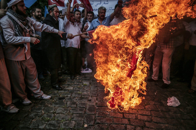 Uighurs living in Turkey set on fire a representation of a Chinese flag outside the Chinese consulate in Istanbul, Turkey, Saturday, Aug. 2, 2014, as they stage a protest to condemn the killings of Uighurs allegedly killed by Chinese security in China's far-western Xinjiang Uighur Autonomous Region. The blue flag with a white star and a crescent represents Eastern Turkistan. (Photo by Emrah Gurel/AP Photo)