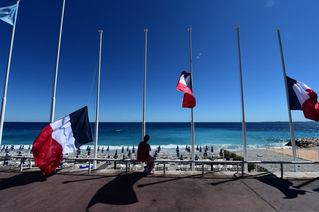 "A woman sits under French flags lowered at half-mast in Nice on July 15, 2016, following the deadly Bastille Day attacks. A Tunisian-born man zigzagged a truck through a crowd celebrating Bastille Day in the French city of Nice, killing at least 84 and injuring dozens of children in what President Francois Hollande on July 15 called a ""terrorist"" attack. (Photo by Giuseppe Cacace/AFP Photo)"