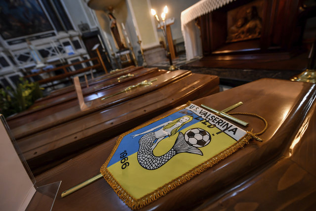 Coffins, one of them with the pennant of the local soccer team, wait to be transported to cemetery, in the church of Serina, near Bergamo, Northern Italy, Saturday, March 21, 2020. Italy's tally of coronavirus cases and deaths keeps rising, with new day-to-day highs: 793 dead and 6,557 new cases. (Photo by Claudio Furlan/LaPresse via AP Photo)