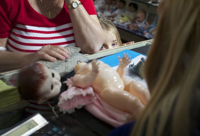 A young customer looks over the counter as a family member brings in a doll for repair at Sydney's Doll Hospital May 20, 2014. (Photo by Jason Reed/Reuters)