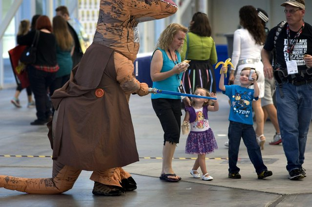 Children look at a person in a dinosaur costume holding a Star Wars lightsaber toy during the Preview Night before the San Diego Comic Con 2016 in San Diego, California, USA, 20 July 2016. (Photo by David Maung/EPA)