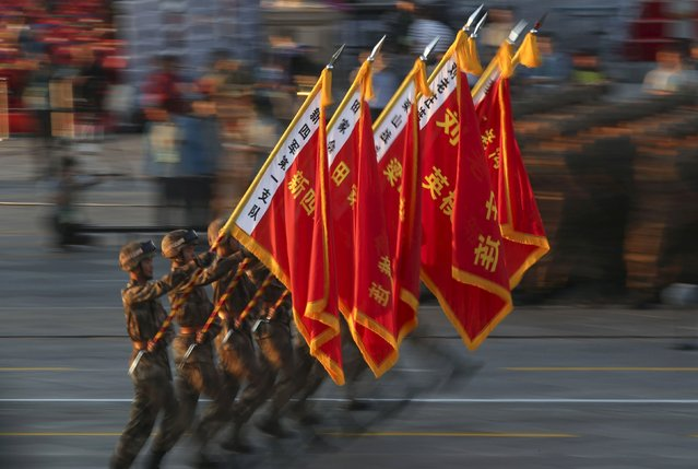 Soldiers of the People's Liberation Army (PLA) of China march with flags displaying names of several PLA's formations during a rehearsal ahead of a military parade to mark the 70th anniversary of the end of World War Two, in Beijing, China, September 3, 2015. (Photo by Reuters/Stringer)