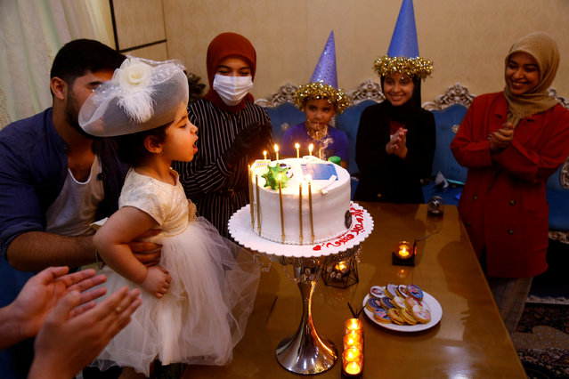 An Iraqi family celebrates their daughter's birthday with a cake with figures of Dettol bottles and models of the coronavirus, during the outbreak of the coronavirus disease (COVID-19), at a cake shop in the holy city of Najaf, Iraq on April 24, 2020. (Photo by Alaa al-Marjani/Reuters)