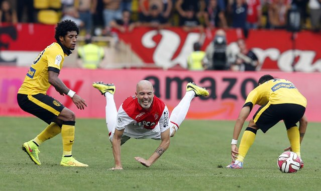 Monaco's Andrea Raggi (C) falls as he is challenged by Lille's Isaac Ryan Mendes (L) during their French Ligue 1 soccer match at Louis II stadium in Monaco, August 30, 2014. (Photo by Eric Gaillard/Reuters)