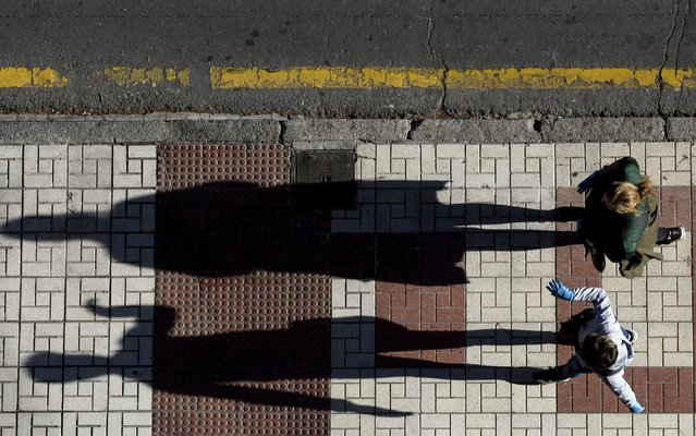 A woman walks with her daughter through an empty street on April 27, 2020 in Malaga, Spain. Since April 27 children under 12 are allowed to come and go from their homes more freely. Spain has had more than 209,000 confirmed cases of COVID-19 and over 23,000 reported deaths, although the rate has declined after weeks of lockdown measures. (Photo by Daniel Perez Garcia-Santos/Getty Images)