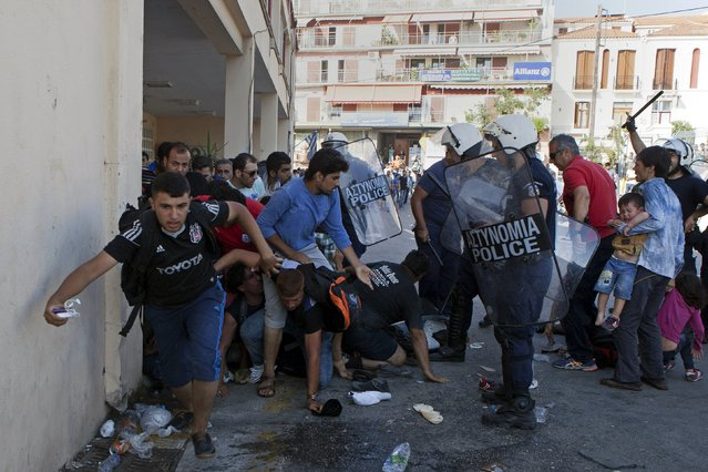 Greek riot police officers disperse Afghan refugees who protested over priority for a registration procedure at the port of Mytilene on the Greek island of Lesbos, September 6, 2015. Greece is struggling to cope with the hundreds of migrants and refugees from the war in Syria making the short crossing every day from Turkey to Greece's eastern islands, including Kos, Lesbos, Samos and Agathonisi. (Photo by Dimitris Michalakis/Reuters)