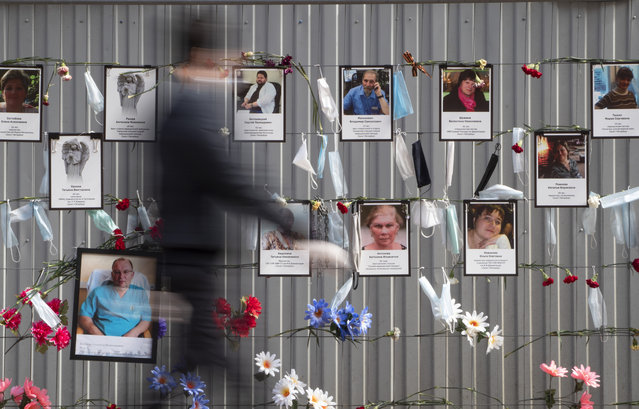 Medical face masks and portraits of St.Petersburg's medical workers who died from coronavirus infection during their work, hang at a unofficial memorial in front of the local health department in St.Petersburg, Russia, Thursday, May 14, 2020. (Photo by Dmitri Lovetsky/AP Photo)