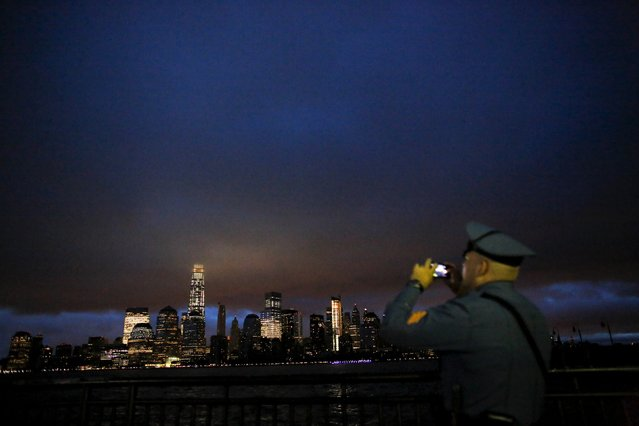 A New Jersey Police Officer takes pictures at sunrise across from New York's Lower Manhattan and One World Trade Center, in Liberty State Park in Jersey City, New Jersey, September 11, 2015. (Photo by Eduardo Munoz/Reuters)