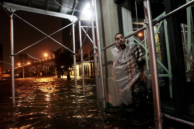 Victor Concepcion stands on a trash can above floodwaters in Brooklyn. (Photo by Kirsten Luce/The New York Times)