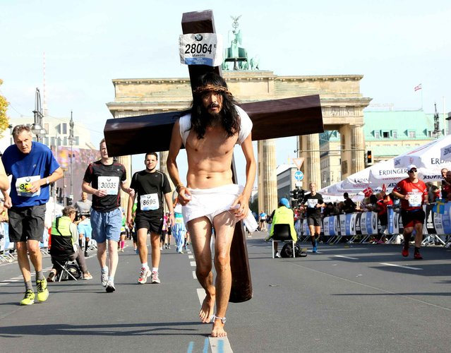 A participant dressed as Jesus runs in front of Brandenburger Gate during the 41th edition of the Berlin Marathon in Berlin on September 28, 2014. (Photo by Stephanie Pilick/AFP Photo/DPA)
