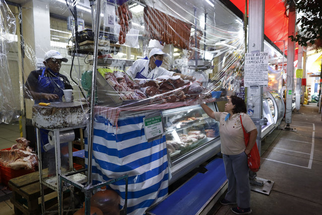 A butcher sells meat to a client from behind a sheet of plastic in Mercado San Cosme, where some vendors decided to put in place protective measures against coronavirus while others continue to work without masks or barriers, in Mexico City, Thursday, June 25, 2020. (Photo by Rebecca Blackwell/AP Photo)