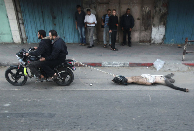 "Palestinian gunmen ride a motorcycle as they drag the body of a man, who was suspected of working for Israel, in Gaza City November 20, 2012. Palestinian gunmen shot dead six alleged collaborators in the Gaza Strip who ""were caught red-handed"", according to a security source quoted by the Hamas Aqsa radio on Tuesday. (Photo by Suhaib Salem/Reuters)"