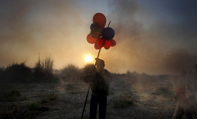 A balloon seller waits for customers on the banks of the Yamuna River during the final day of the Chhath Puja festival in New Delhi, November 20, 2012. The ancient Hindu festival is celebrated to thank the Sun God for sustaining life on earth. (Photo by Altaf Qadri/Associated Press)