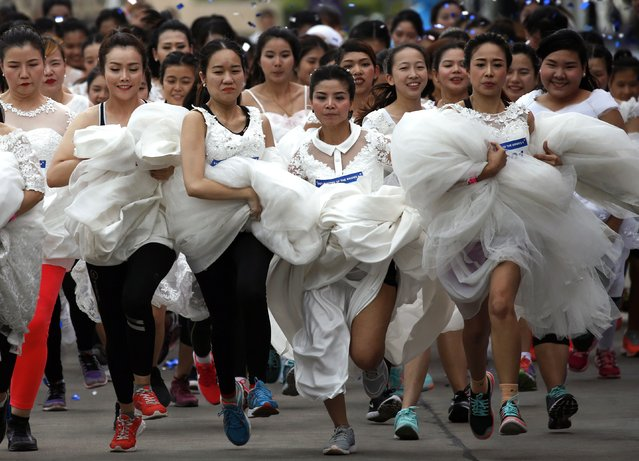 """Thai brides-to-be compete in the """"Running of the Brides"""" event in Bangkok, Thailand, 02 December 2017. Six hundred of to be brides and their grooms compete a run race aimed to win more than two million baht (61,000 US dollars or 51,000 euro) of wedding package prizes including a pair of white gold diamond rings and honeymoon trip to the Maldives. (Photo by Rungroj Yongrit/EPA/EFE/Rex Features/Shutterstock)"""