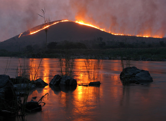 """The Congo River, deep in the Democratic Republic of Congo: Downstream from the infamous ""Gates of Hell"" rapids on the Congo river, this was the view from my camp during my five month canoe trip from source to sea. The grass covered hills were being burnt down for farming in the background"". (Photo and comment by Phil Harwood/National Geographic Photo Contest via The Atlantic)"