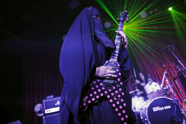 Gisele Marie, a Muslim woman and professional heavy metal musician, plays her Gibson Flying V electric guitar during a concert in Sao Paulo December 16, 2014. Based in Sao Paulo, Marie, 42, is the granddaughter of German Catholics, and converted to Islam several months after her father passed away in 2009. (Photo by Nacho Doce/Reuters)