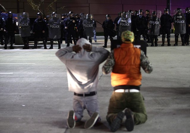 Demonstrator protesting the shooting death of Michael Brown and 18-year-old Vonderrit Myers Jr. kneel as they face police officers in riot gear in St. Louis, Missouri on October 12, 2014. Thousands of people took to the streets of the midwestern US city of St Louis on October 12 to protest police tactics in the wake of the racially charged shooting of an unarmed black teenager. (Photo by Joshua Lott/AFP Photo)