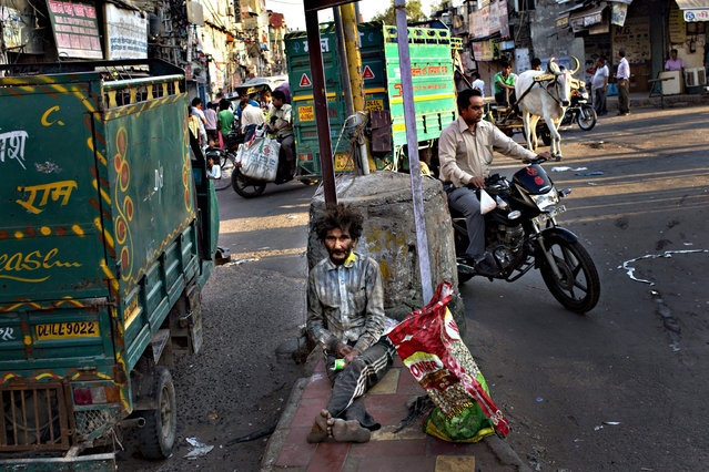 A homeless Indian man sits at a traffic intersection in the morning in New Delhi, India, Wednesday, September 30, 2015. Hundreds of millions of Indians still live on less than $2 a day. The United Nations global goals for sustainable development in the next fifteen years, seeks to end poverty in all its forms everywhere. (Photo by Bernat Armangue/AP Photo)