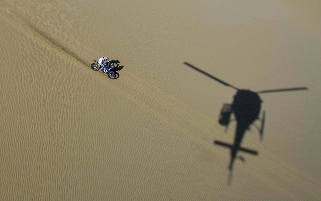 A helicopter casts a shadow on the ground as Yamaha rider David Casteu of France competes in the 2nd stage in Pisco, Peru. (Photo by Franck Fife/Associated Press)