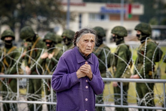 An elderly lady walks by serviceman standing behind a barbed wire fence during a protest in Minsk, Belarus, Sunday, August 23, 2020. Demonstrators are taking to the streets of the Belarusian capital and other cities, keeping up their push for the resignation of the nation's authoritarian leader, president Alexander Lukashenko, in a massive outburst of dissent that has shaken the country since dubious presidential elections two weeks ago.(Photo by Dmitri Lovetsky/AP Photo)