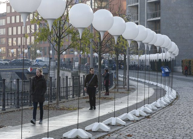 """People walk under stands with balloons placed along the former Berlin Wall location by the Spree river, which will be used in the installation """"Lichtgrenze"""" (Border of Light) in Berlin November 7, 2014. (Photo by Fabrizio Bensch/Reuters)"""