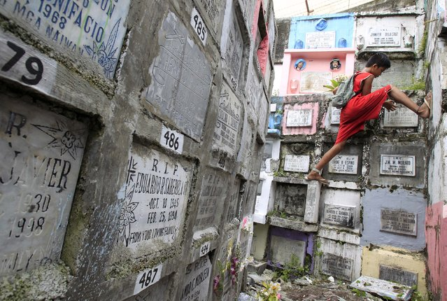 A boy cleans the gravestone of a loved one at a public cemetery in Marikina city, east of Manila November 1, 2014. (Photo by Romeo Ranoco/Reuters)