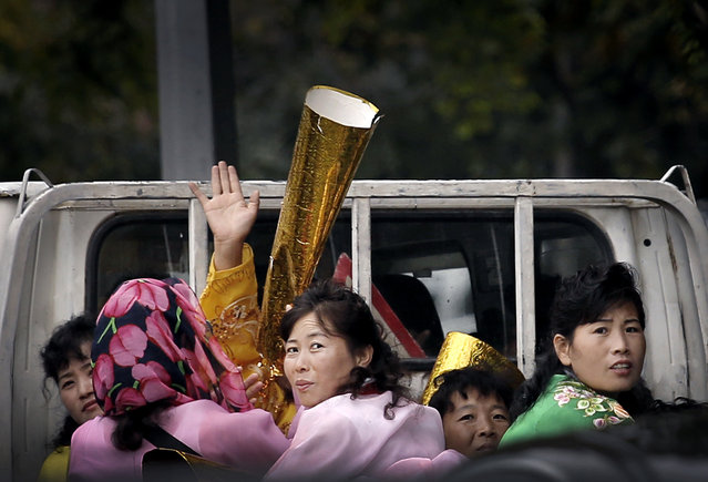 North Koreans riding on the back of a pickup truck carry props to be used during upcoming anniversary celebrations, Thursday, October 8, 2015, in Pyongyang, North Korea. The country is in high gear with preparations for the 70th anniversary of the founding of North Korea's Workers' Party on Oct. 10. 2015. (Photo by Wong Maye-E/AP Photo)