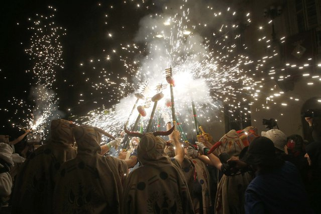 """Revellers dressed in devil costumes light fireworks during the """"Les Santes"""" (The Saints) festival in Mataro, near Barcelona July 20, 2014. The wealthy northeastern region of Catalonia last month dropped plans for a non-binding referendum on independence from Spain on Nov. 9 after a court declared such a vote against the constitution and had instead planned to hold a """"consultation of citizens"""" on the same day. (Photo by Gustau Nacarino/Reuters)"""