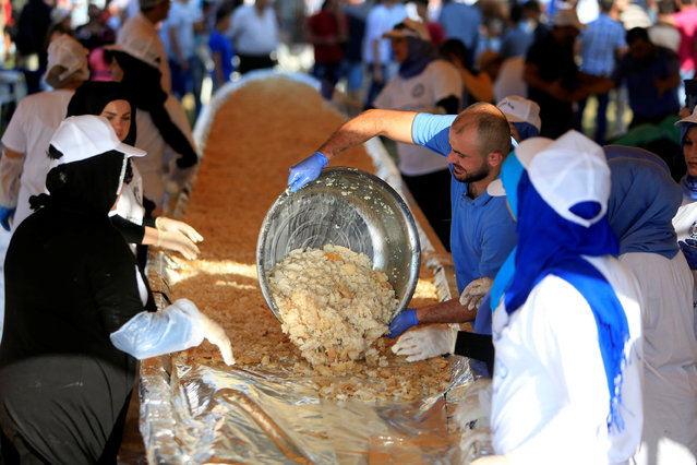 A man pours cooked fish into a huge container during an attempt to enter the Guinness Book of World Records for the largest spicy fish plate in Sarafand, South Lebanon September 16, 2016. (Photo by Ali Hashisho/Reuters)