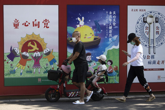 """A man wearing a mask to protect from the coronavirus pushes an electric bike with a child past propaganda posters with the words """"Childlike devotion to the Party"""" in Beijing on Wednesday, September 2, 2020. (Photo by Ng Han Guan/AP Photo)"""