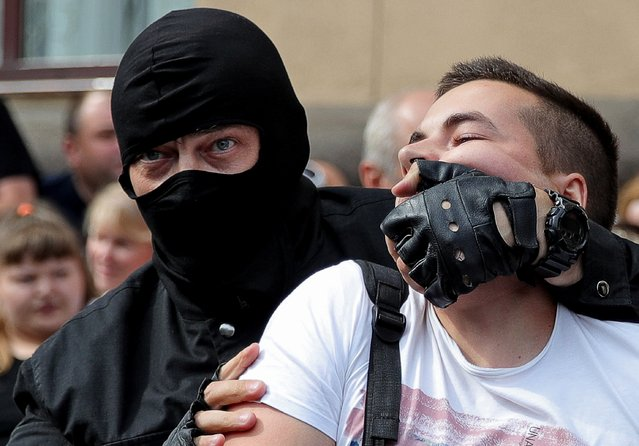 A riot police officer detains a Belarussian opposition supporter during a protest in Independence Avenue in Minsk, Belarus on August 30, 2020. The announcement of the results of the 2020 Belarusian presidential election has sparked mass protests in Minsk and major cities across Belarus. (Photo by Sergei Bobylev/TASS)